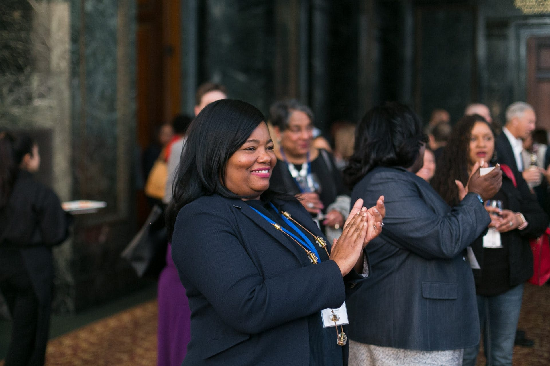 Female-presenting black woman clapping and wearing a suit jacket and event lanyard