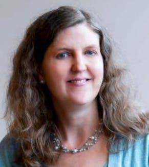 A headshot of Laura Hamilton, a female-presenting person, who smiles towards the camera.