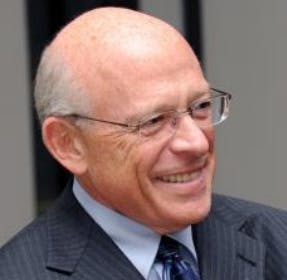 A headshot of Sheldon Berman, a male-presenting person, who smiles away from the camera.