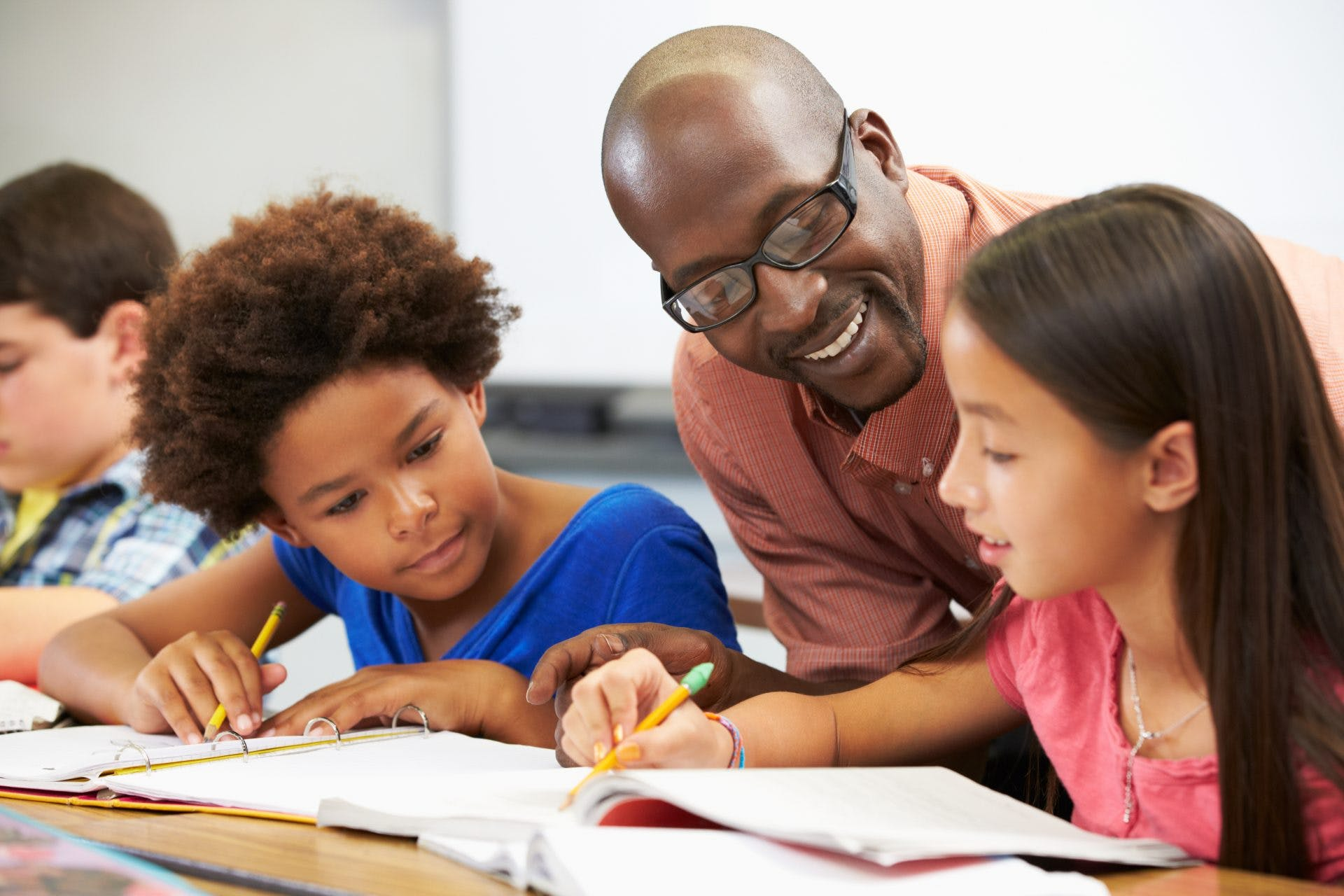 A male presenting teacher helping two children with school work.